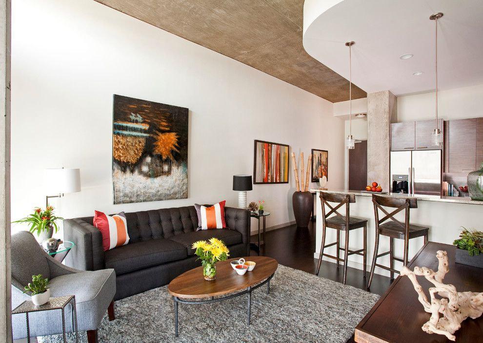 Черный диван вдоль белой стены кухни-гостиной