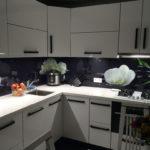 Крупные цветки белого цвета на стеклянном фартуке кухни