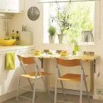 Маленький обеденный стол перед кухонным окном