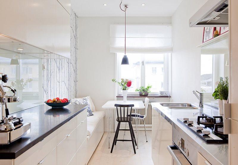 Обеденная зона узкой кухни с диванчиком у стены
