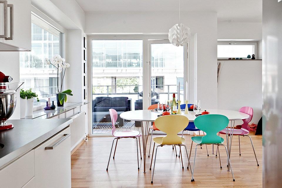 Стулья разных цветов в кухне с белыми стенами