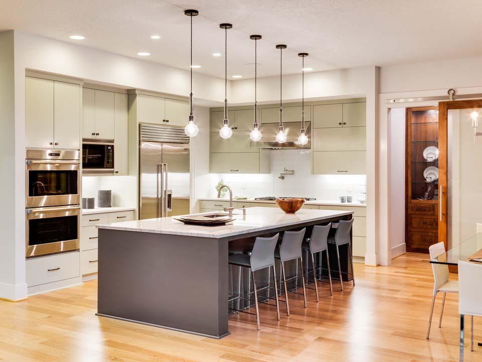 Подвесные светильники над барной стойкой в кухне-столовой