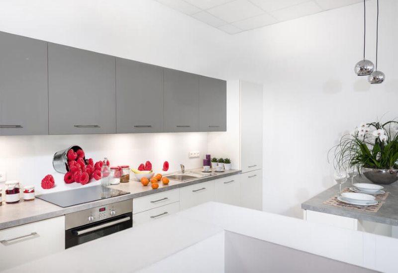 Серые подвесные шкафчики над стеклянным фартуком кухни