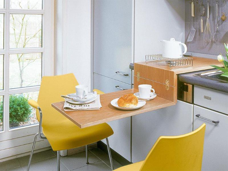 Желтые стулья за выдвижным столиком в кухне