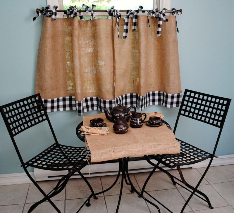 Столик для завтраков перед кухонным окном с короткой занавеской