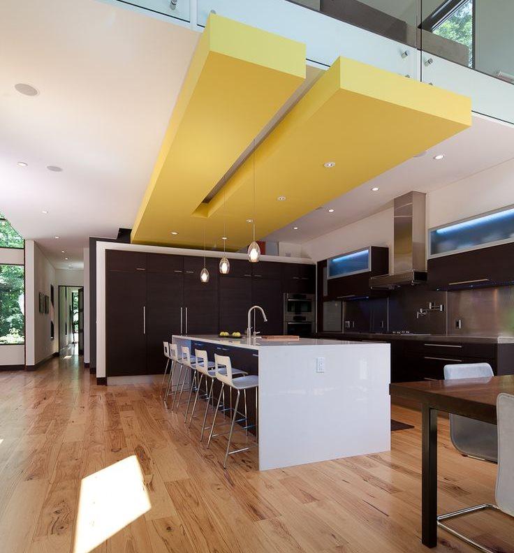 Желтая конструкция на потолке кухни-столовой в частном доме