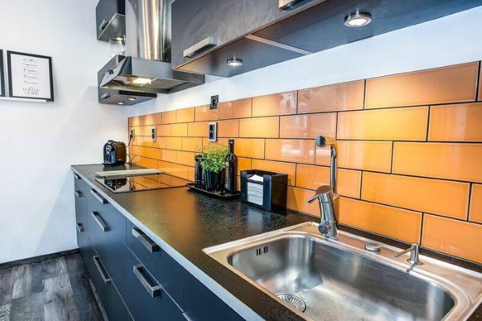 Оранжевая плитка на фартуке линейной кухни
