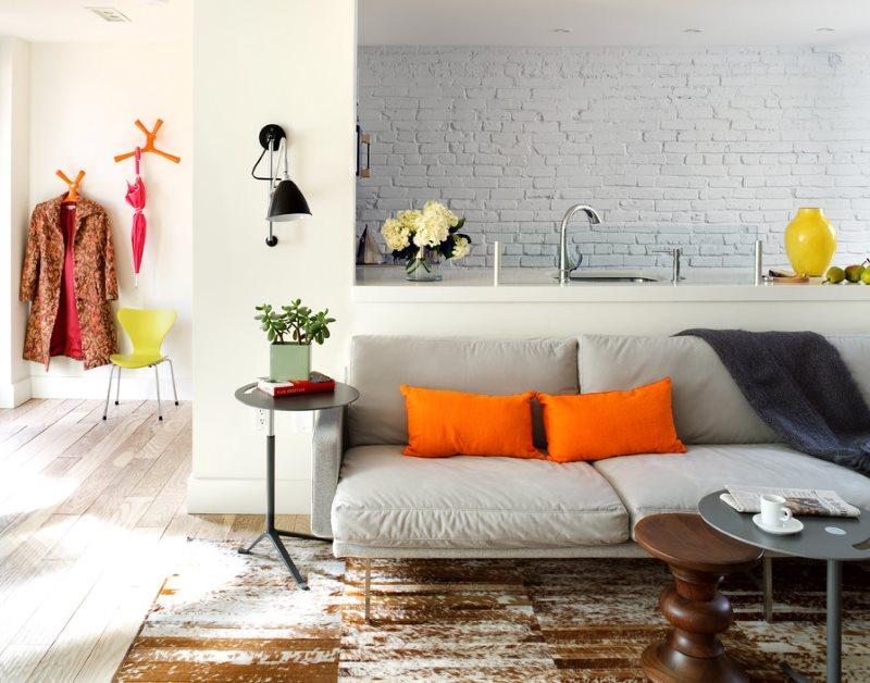 Оранжевые подушки на сером диване в кухне-гостиной