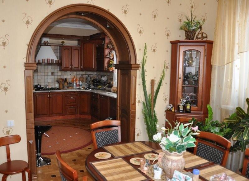 Обеденный стол в комнате с деревянной аркой