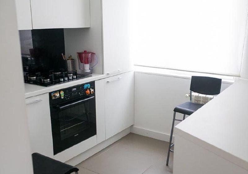 Черная техника в маленькой кухне с белой мебелью