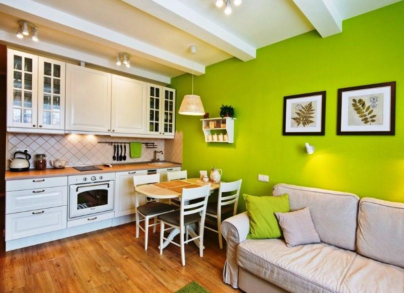 Зеленая стена в кухне-гостиной с белым гарнитуром