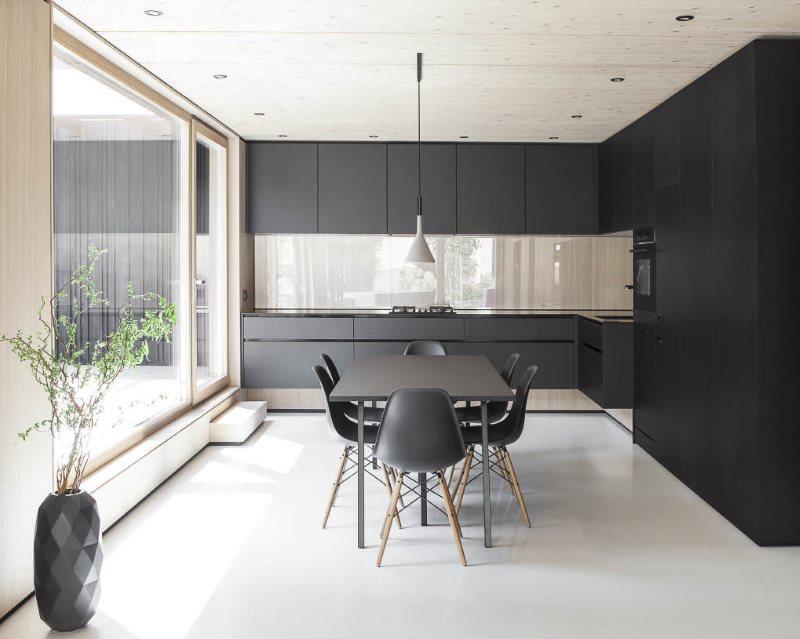 Угловой гарнитур черного цвета на кухне в стиле минимализма