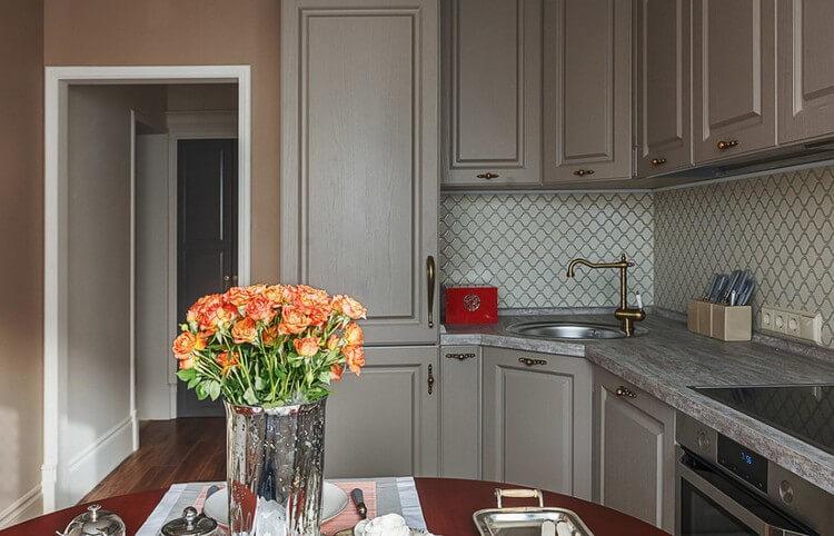 Живые цветы в стеклянной вазе на кухонном столе