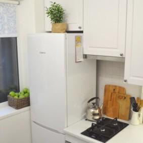 Белый холодильник возле окна кухни