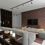 Серая мебель в комнате с кирпичной стеной