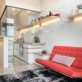 Красный диван вдоль стены кухни-гостиной