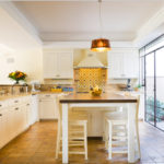 Включенный светильник на потолке кухни