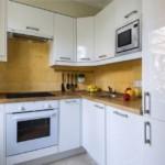 Желтая плитка квадратной формы на кухонном фартуке