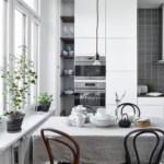 Обеденный стол возле окна кухни без занавесок