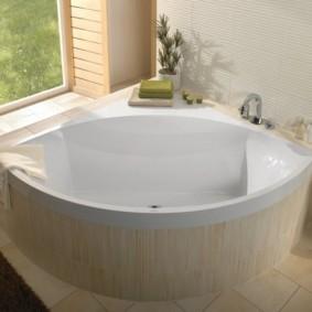 Угловая ванна из акрила перед окном в частном доме