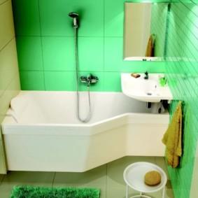 Белая сантехника в ванной с зелеными стенами
