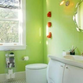 Белый унитаз в комнате с зелеными стенами
