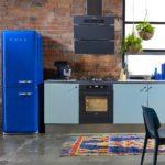 Синий холодильник на фоне кирпичной стены