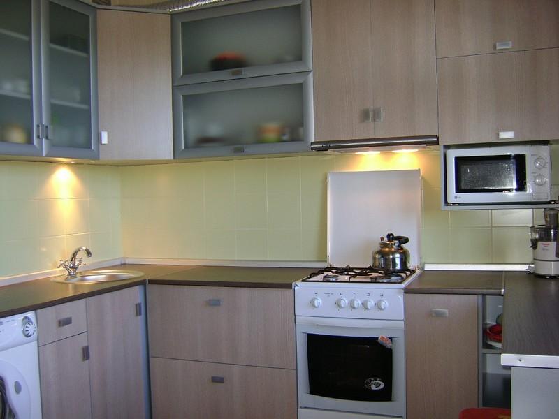 Белая газовая плита в угловой кухне