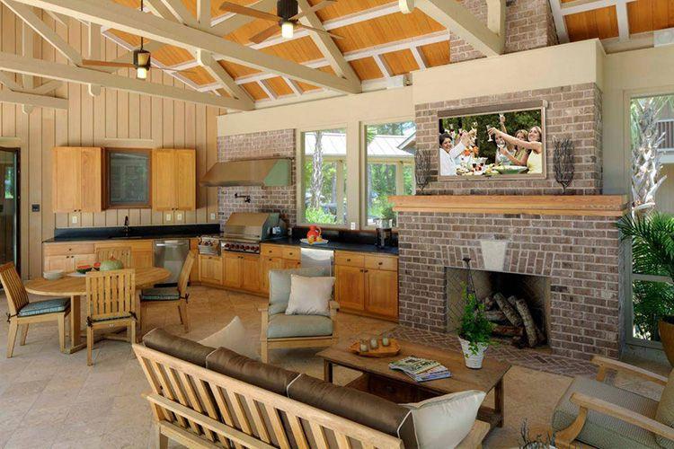 Интерьер просторной летней кухни с камином