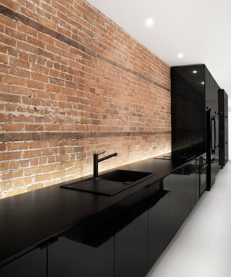 Черный глянцевый гарнитур вдоль кирпичной стены кухни
