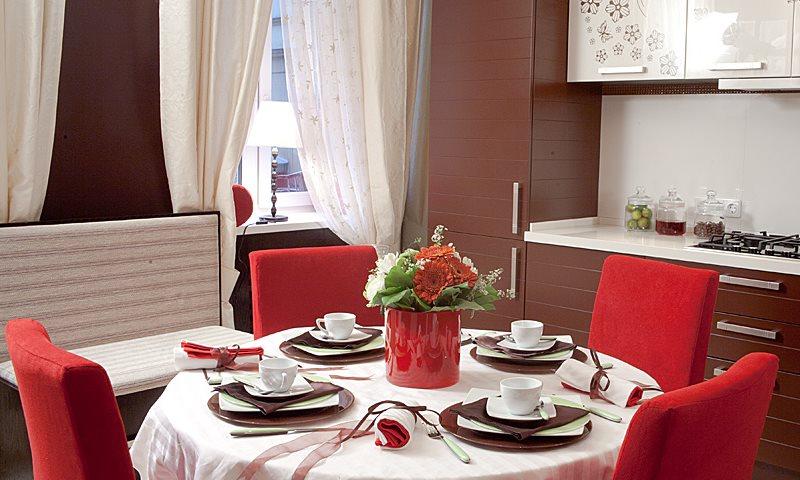 Красные спинки стульев в кухне с шоколадным гарнитуром
