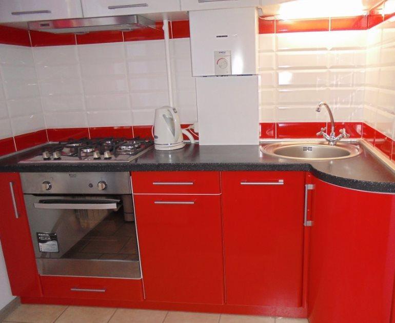 Белая газовая колонка и красный кухонный гарнитур