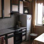 Низкий холодильник около кухонного окна