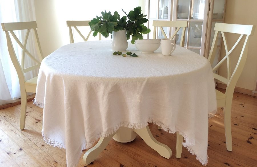 Белая скатерть с бахромой на деревянном столе
