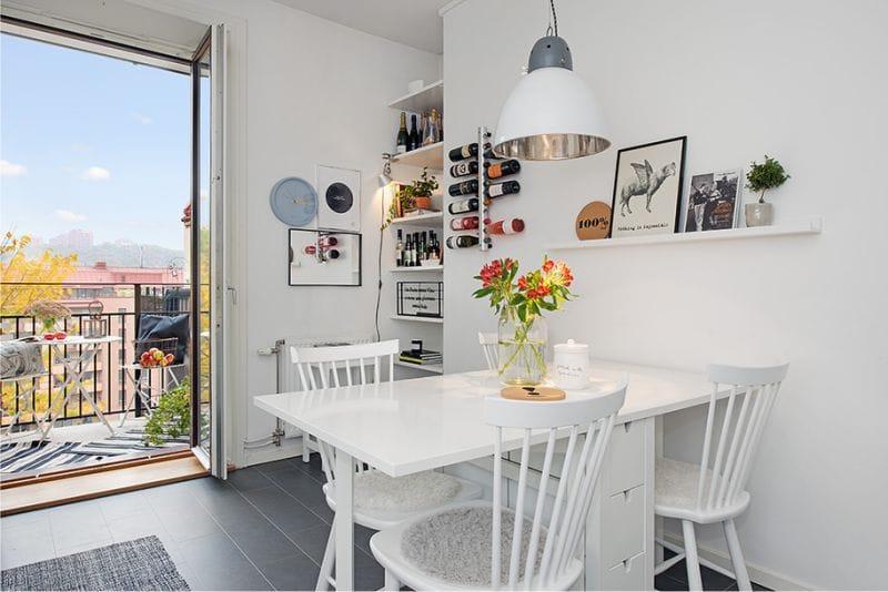 Белый стол в обеденной зоне угловой кухни