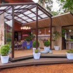 Растения в вазонах на деревянном полу летней кухни