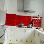 Красный фартук в кухне с белым гарнитуром