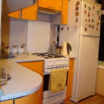 Белый холодильник в конце гарнитура с оранжевыми фасадами