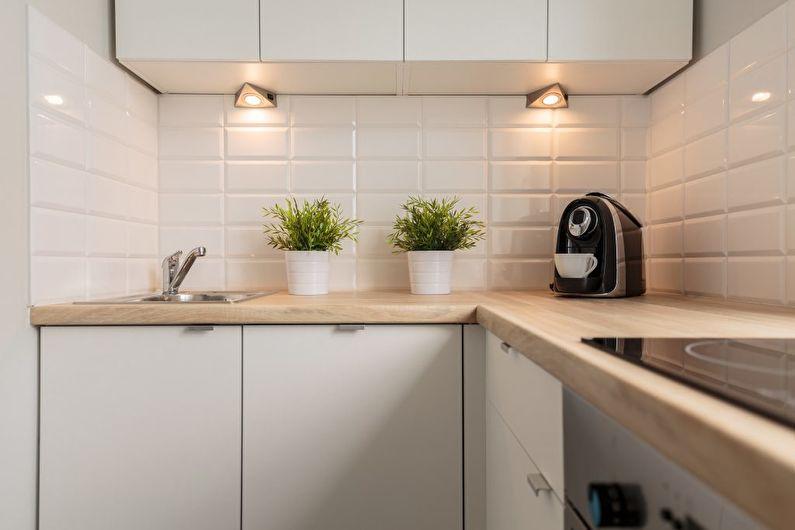 Небольшие светильники под навесными шкафчиками в компактной кухне