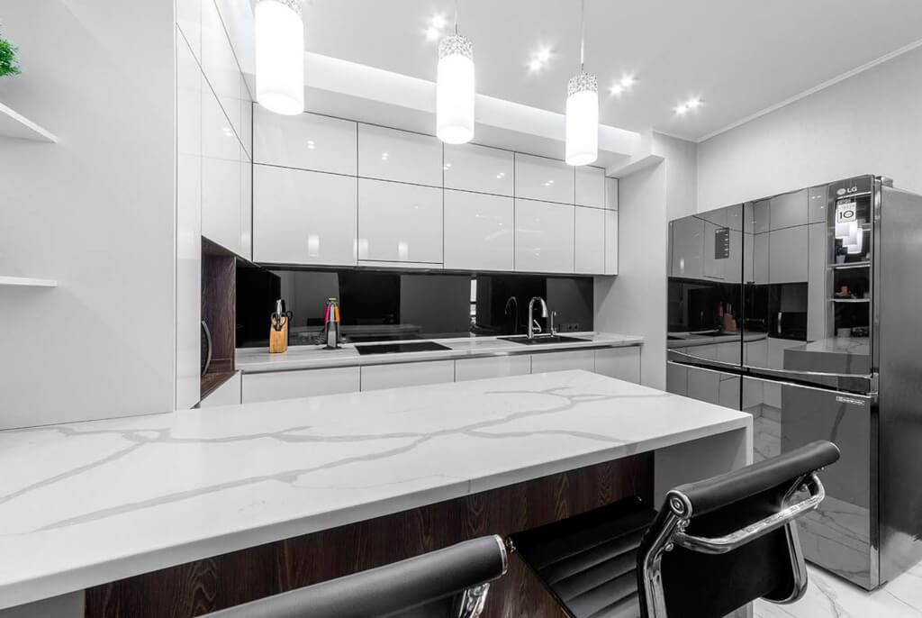 Яркое освещение модной кухни угловой планировки