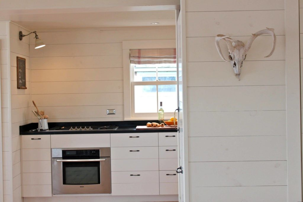 Белые панели из пластика на стене кухни частного дома