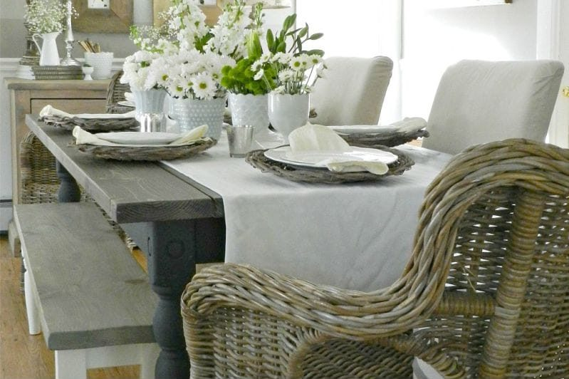 Плетенное кресло около деревянного стола с грубой отделкой