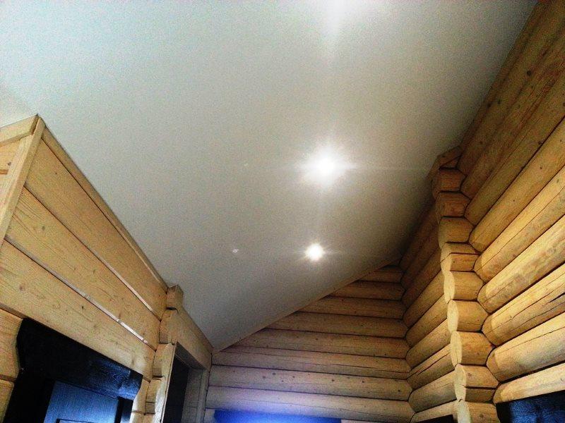 Ровная поверхность потолка из гипсокартона в доме из бревен
