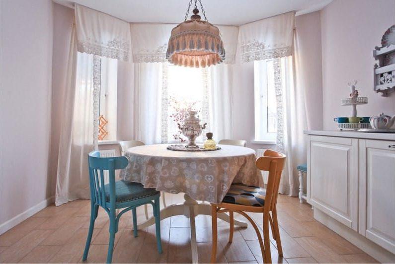 Разные стулья за кухонным столом с клеенкой