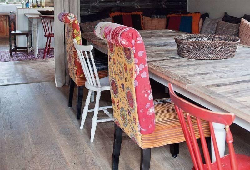 Разные стулья в обеденной зоне кухни-гостиной в стиле кантри