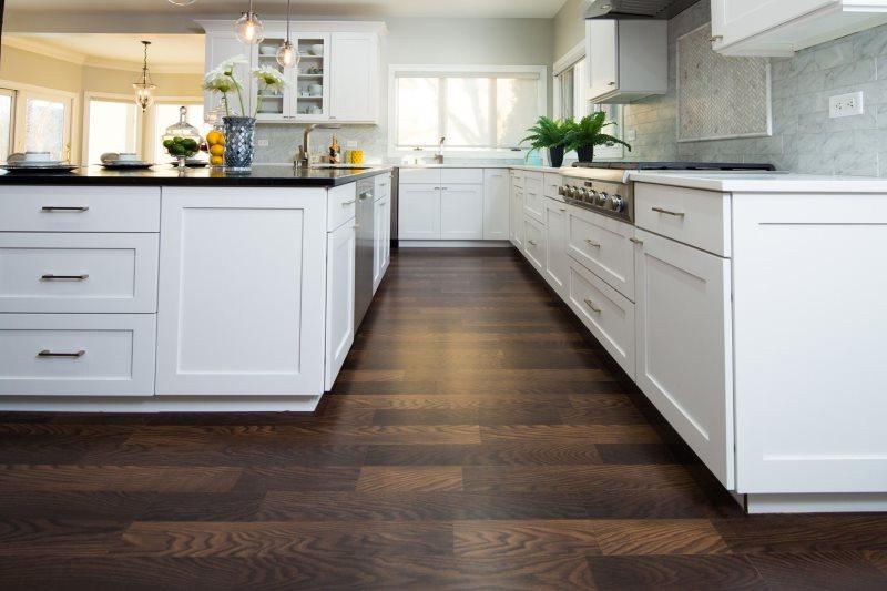 Деревянный пол шоколадного цвета в кухне с белой мебелью