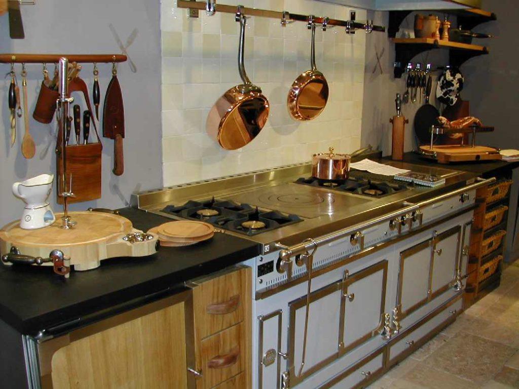 Медные сковородки на рейлинге в кухне деревенского стиля