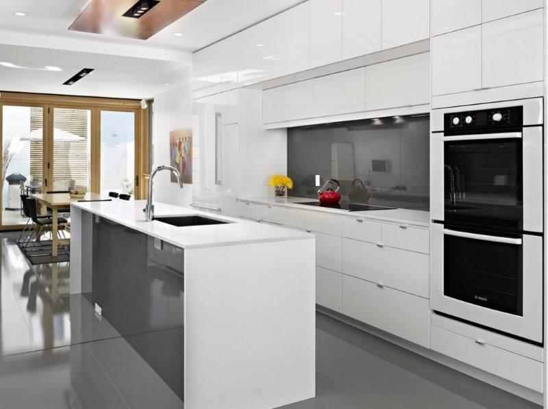 Серая поверхность стеклянного фартука в просторной кухне