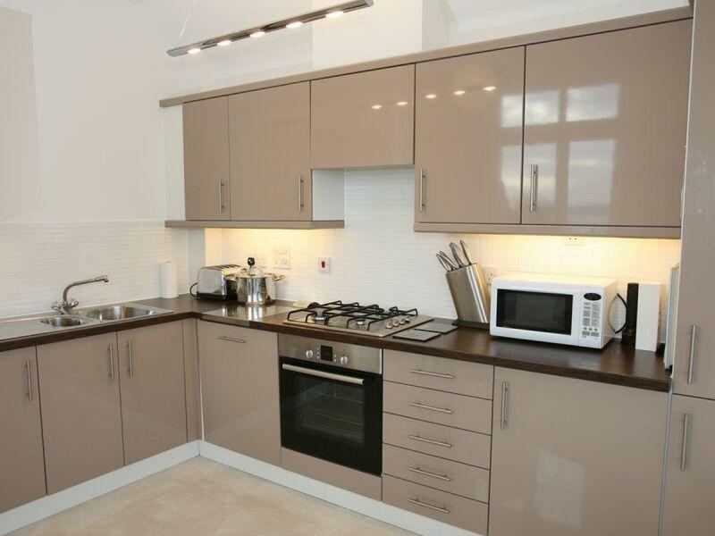 Угловая кухня с коричневой кухней и фасадами капучино