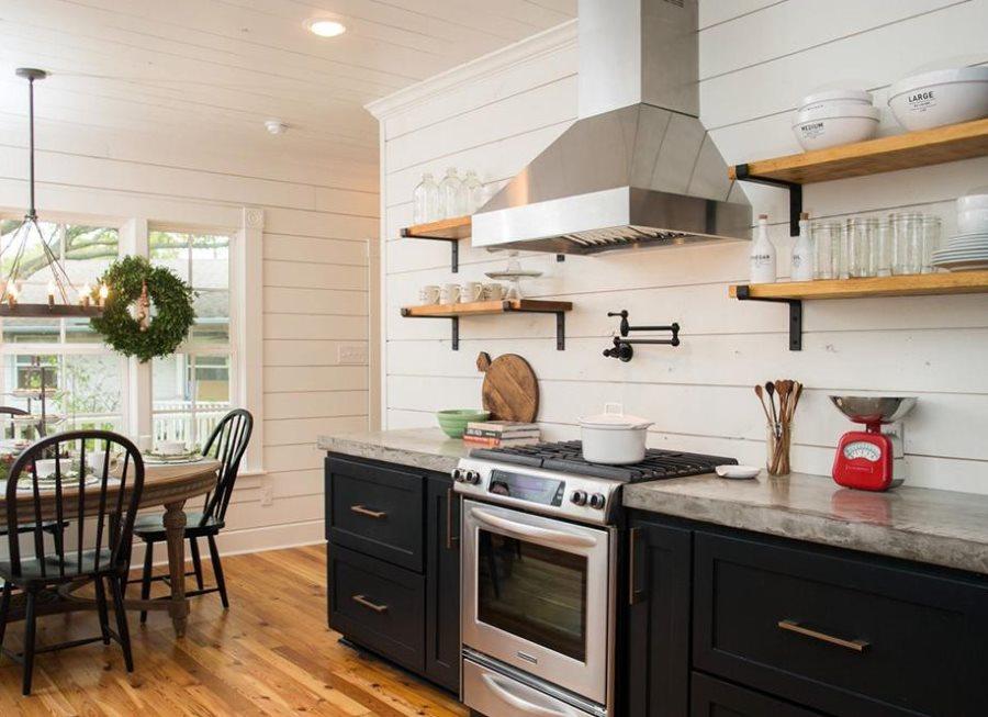 Металлическая вытяжка на стене кухни между деревянными полками
